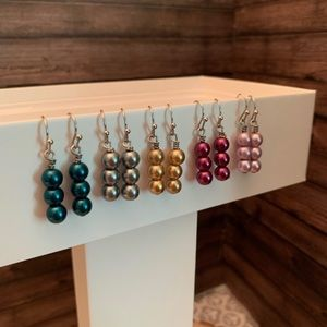 Five pairs of triple layered pearl earrings